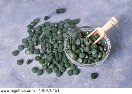 Green Pills Of Spirulina Or Chlorella On A Gray-blue Plaster Background In A Glass Bowl And In A Woo