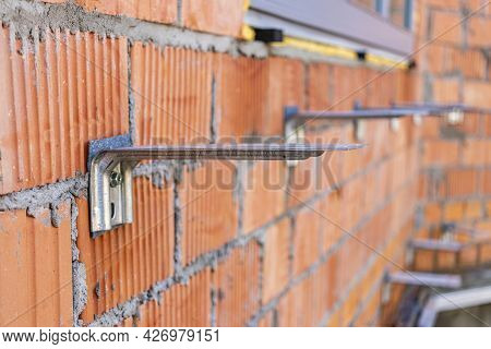 Fastening For Insulation On A Brick Wall Of A House Under Construction. Installation Of Fittings For