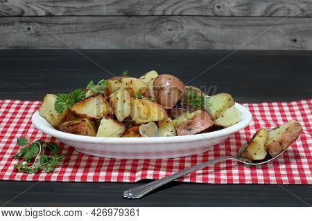 An Oval Bowl Of Roasted Red Potatoes With Onions, Oregano And Parsley.  Close Up With Copy Space.