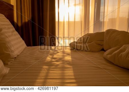 Bed With White Linens At Sunrise.sleeping Place With Pillows And A Blanket At Dawn.resvet In The Bed