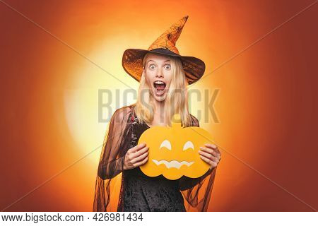 Halloween Decoration And Scary Concept. Happy Gothic Young Woman In Witch Halloween Costume With Hat