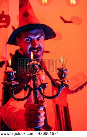 Handsome Man In Wizard Costume Hat For Halloween On Fairytale Background. Halloween, Holidays Celebr