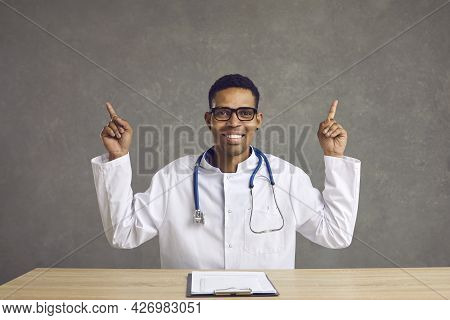 Happy Smiling African American Doctor Sitting At Desk Pointing Forefinger Up