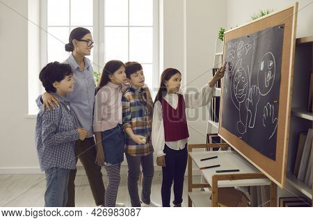 Elementary School Girl Student Answering At Board On Lesson Front Of Classmates