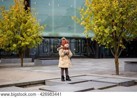 Full Length Portrait Of Cute Little Girl Walking In Autumn City Park