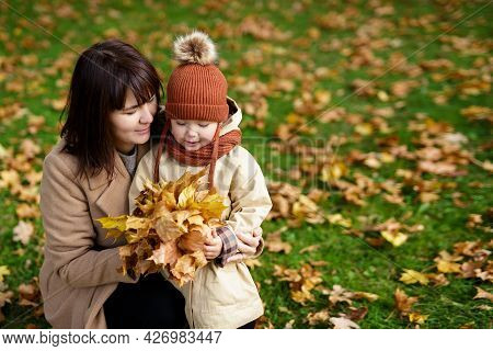 Family, Motherhood, Love And Care Concept - Portrait Of Mother And Her Little Daughter Walking In Au