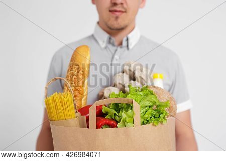 Food Delivery Concept - Close Up Of Paper Bag Full Of Products In Male Hands Over White Background