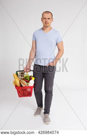 Young Man With Shopping Basket Full Of Products Walking Over White Background