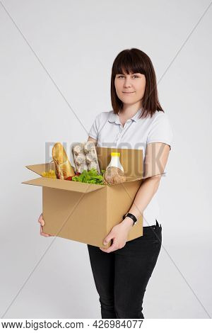 Food Delivery Or Donation Concept - Portrait Of Young Woman Posing With Cardboard Box Full Of Produc