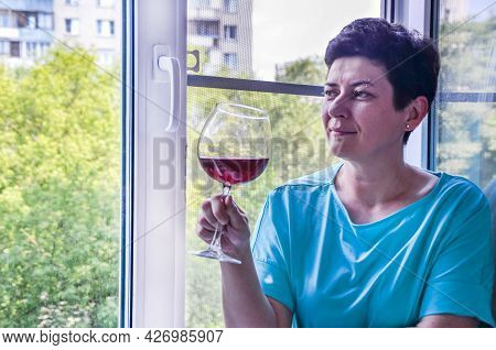 Attractive Brunette Woman With Short Hair Sits On Windowsill And Dreamily Looks Out Window, Holding
