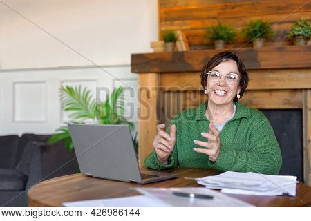 Smiley 60-years-old Woman Is Online Working In Front Of Laptop Monitor