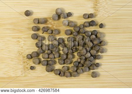 Jamaica Pepper On Wooden Bamboo Background, Traditional Spices. Allspice Close-up. Selective Focus