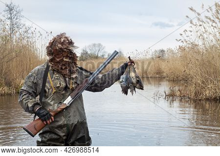 The Hunter Is Standing In The Middle Of A Deep Lake Overgrown With Reeds. He Holds In His Hands His