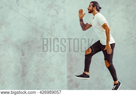 Crazy Young Man Jumping In Casual White T-shirt Posing Isolated On Grey Wall Background. People Life