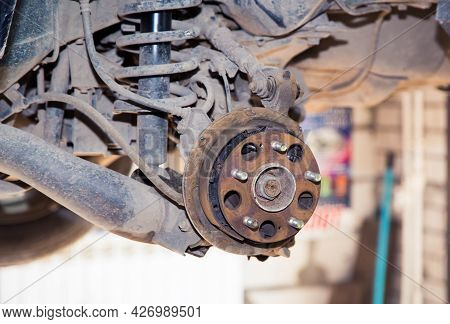 Rusty Hub And Rear Suspension On A Raised Vehicle. In The Garage, A Man Changes Parts On A Vehicle.