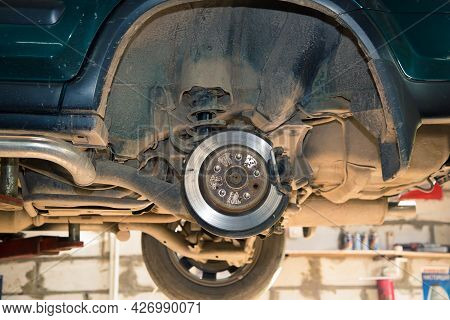 Rear Wheel Hub Of A Car Lifted On A Lift. In The Garage, A Man Changes Parts On A Vehicle. Small Bus