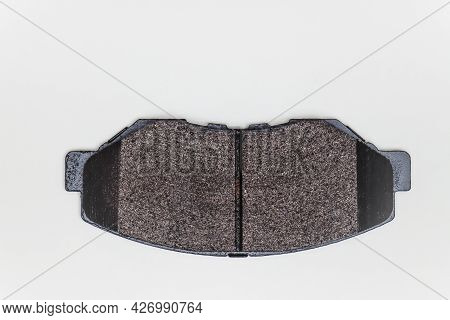 One Brake Pad On A Flat Surface. Set Of Spare Parts For Car Brake Repair. Details On White Backgroun