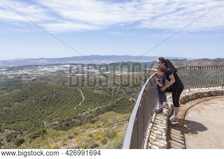 Child About 4-5 Years Old With His Mother Observing From A Lookout On The Heights, While The Mother