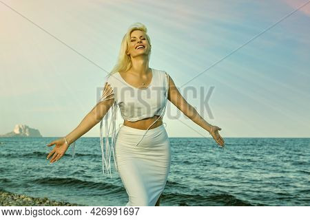 Long-haired Blonde Woman Dressed In White, Enjoying The Sea Breeze By The Sea With Her Eyes Closed A