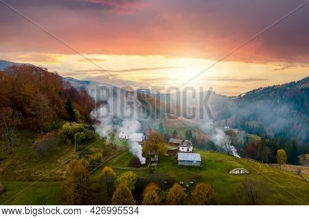 Aerial View Of Small Shepherd Houses On Wide Meadow Between Autumn Forest In Ukrainian Carpathian Mo