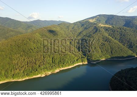 Aerial View Of Big Lake With Clear Blue Water Between High Mountain Hills Covered With Dense Evergre
