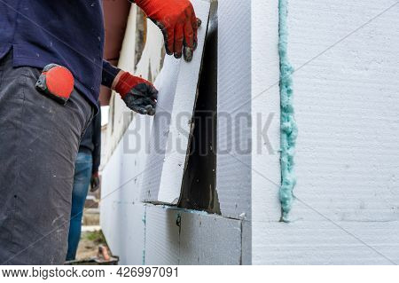 Construction Worker Installing Styrofoam Insulation Sheets On House Facade Wall For Thermal Protecti