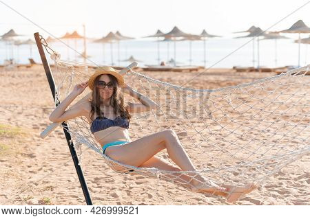 Enjoying Summer Vacation. Young Happy Woman Wearing Straw Hat And Sunglasses Keeping Eyes Closed And