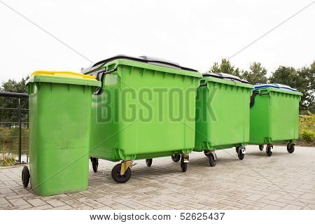 Green garbage containers in a row