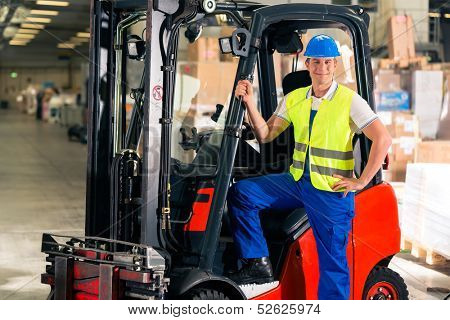 forklift driver in protective vest and forklift standing at warehouse of freight forwarding company, smiling