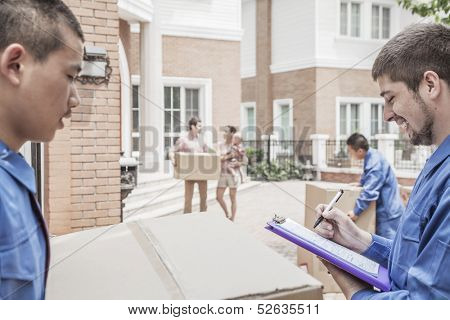 Mover holding clipboard and invoice with family in the background