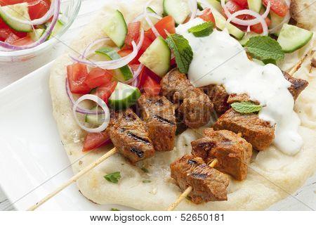 Tandoori lamb kebabs with naan bread, salad, and minted yogurt.