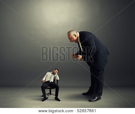 big angry boss screaming at small lazy worker
