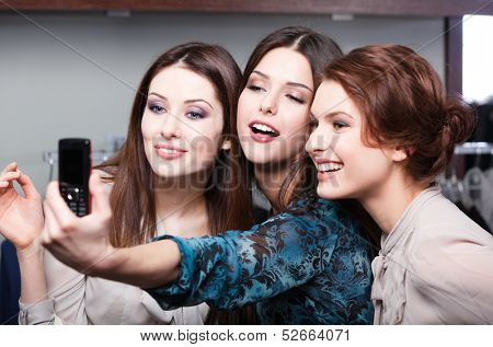 Smiling girls photo session on the mobile phone after shopping
