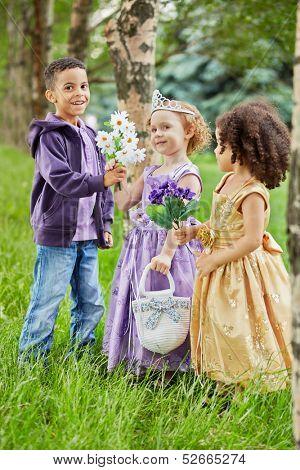 Three children in summer park, boy presents glowers to girl