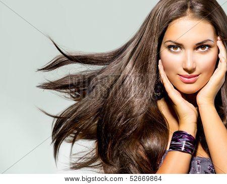 Beautiful Woman with Long Brown Hair. Blowing Hair. Closeup portrait of a Fashion Model Girl. Studio Shot