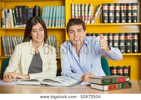 Portrait of happy male student gesturing thumbsup while friend reading book at table in college library