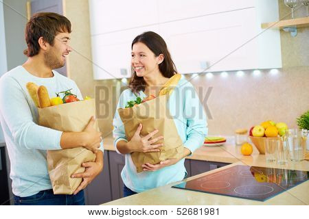 Pretty female and her husband holding packs with products in the kitchen