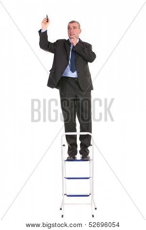 full length picture of a business man standing on a ladder and writing on an imaginary screen while holding his hand at his chin and looking away. on a white background