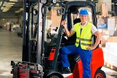forklift driver in protective vest and forklift standing at warehouse of freight forwarding company, smiling poster