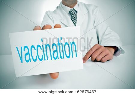 a man wearing a white coat showing sitting in a desk a signboard with the word vaccination written in it poster