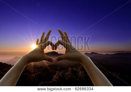 A power of sunrise above a mountain peak looks warm in a calm morning best landscape hand shaking in heart shape poster