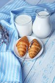 Homemade yogurt in jug and tasty croissants on wooden table background poster