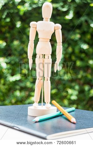 Wood Mannequin Standing On Artist Work Paperbook