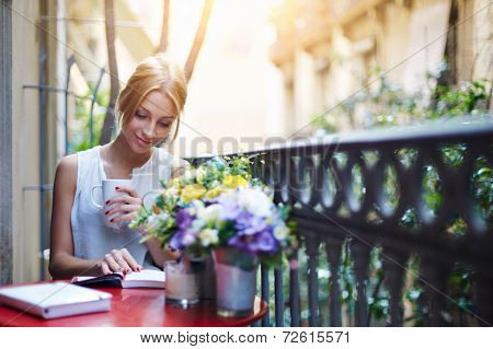 Young woman reading book while sit at terrace table on her balcony, attractive woman reading book