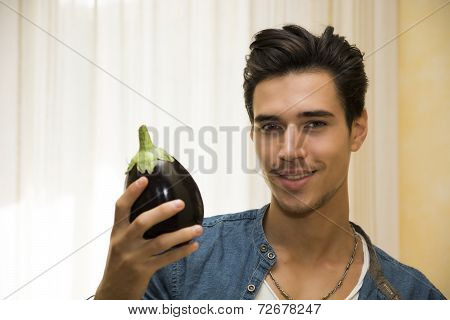 Smiling Young Man Holding A Fresh Eggplant
