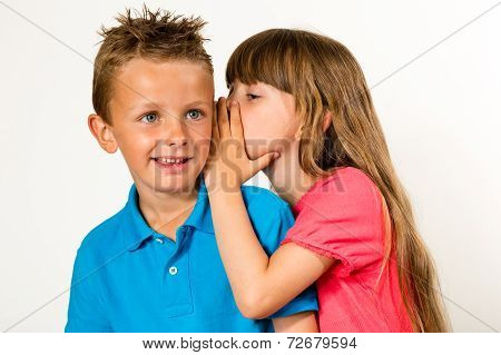 A young girl telling a secret to a young boy. Isolated on white background. poster