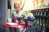 Attractive young girl reading book while drinking coffee at sunny day sitting on the balcony, beautiful young woman with cup of coffee on home balcony reading the book, female student reading book poster