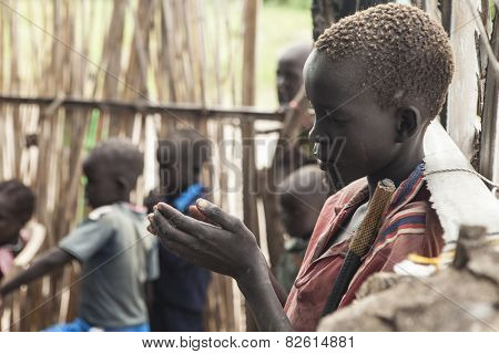 PANWELL, SOUTH SUDAN-NOVEMBER 2, 2013: An unidentified child prays in an outdoor church in South Sudan