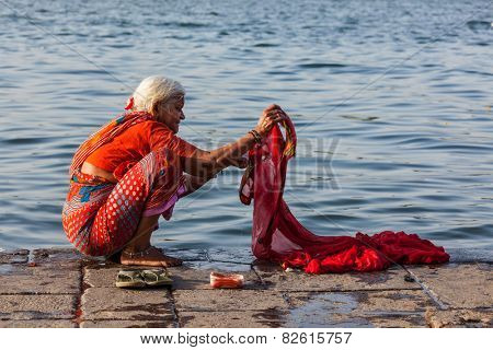 MAHESHWAR, INDIA - APRIL 26, 2011: Old Indian woman washing sari on sacred river Narmada ghats. To Hindus Narmada is one of 5 holy rivers of India
