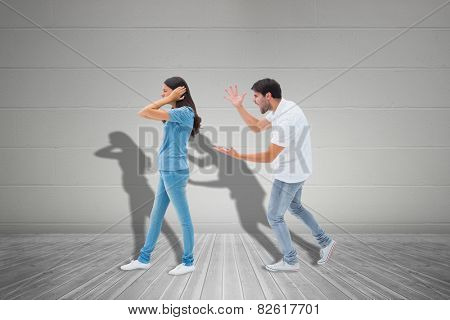 Angry boyfriend shouting at girlfriend against grey room